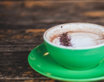A latte in a green cup and saucer on a rustic wood table.